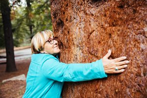 Older woman hugging a tree