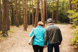 Older couple walking through the woo