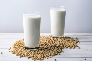 Raw soy seeds and glass of milk on s