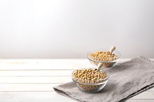 Raw soy seeds in a glass bowl on sla
