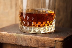 Glass of whiskey near a barrel