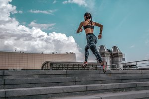 The girl athlete jumps up stairs
