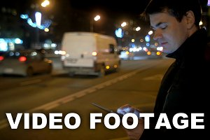Man using touch pad by the busy road