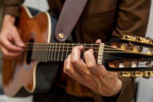 musician plays guitar close up