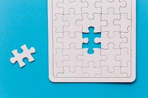 Unfinished white jigsaw puzzle piece