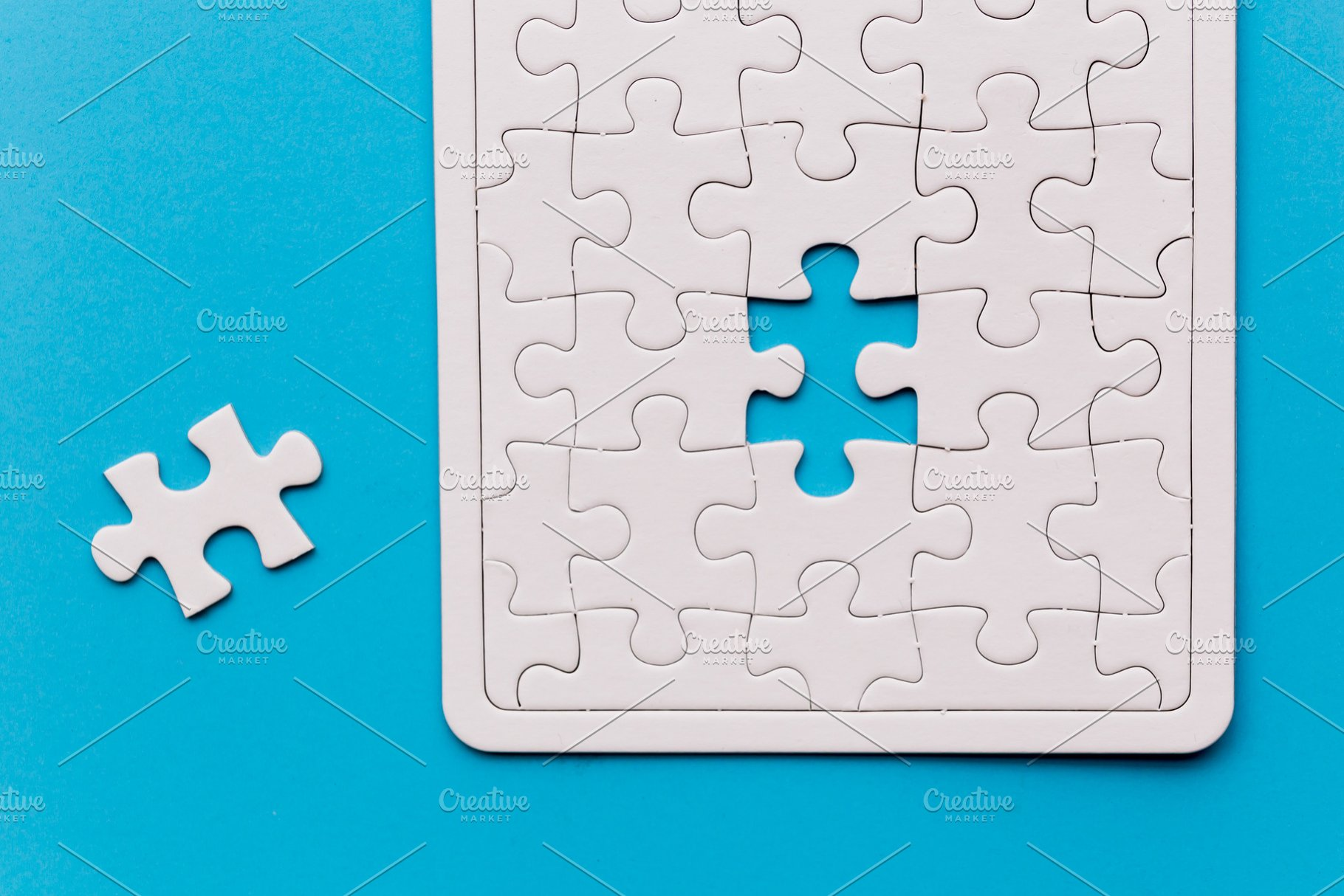 Unfinished white jigsaw puzzle piece