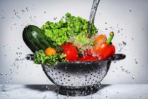 vegetables in a colander under runni
