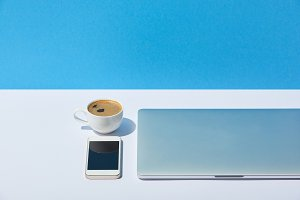 laptop, coffee cup and smartphone on