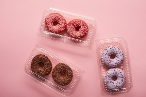 top view of tasty donuts on pink bac