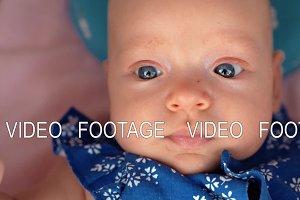 Portrait of baby girl in blue onesie
