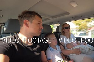 Family of four traveling by car in