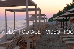 Sea and beach with empty sunbeds at