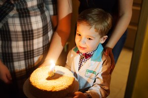 Little boy carrying birthday cake