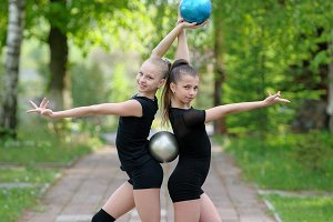 Gymnast girls posing with balls
