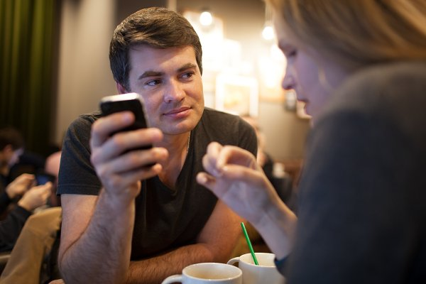 Man using mobile phone girl cafe