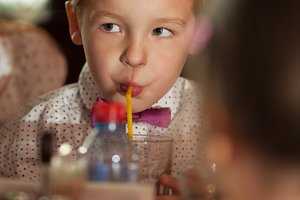 Little boy drinking with tubule