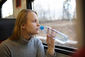 Woman drinking water and looking