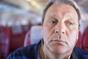 Man listening to music in airplane