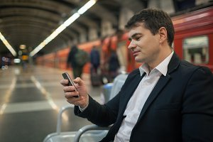 Businessman with smartphone subway