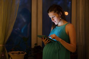 Pregnant woman using tablet