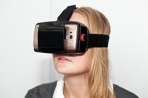 Woman wearing VR-headset over white