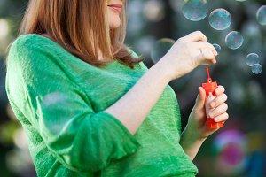 Pregnant woman blowing bubbles