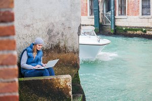 Young woman using laptop by canal