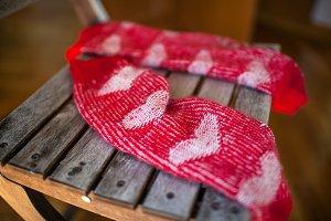 Red woollen socks on wooden chair