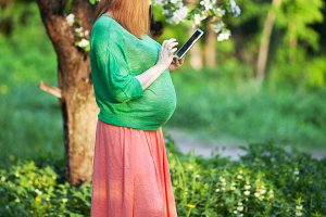 Pregnant woman using tablet PC