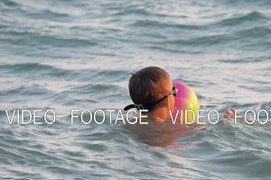 Child is happy to swim on sea waves