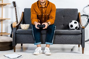 cropped view of man sitting on sofa