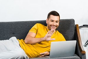 handsome man lying on sofa and wavin