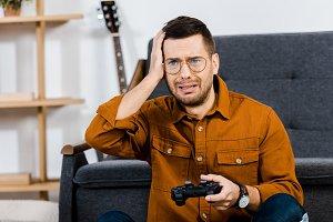 upset man in glasses holding gamepad