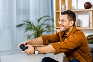happy man in glasses playing video g