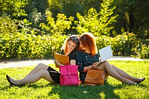 Two female students sit on lawn