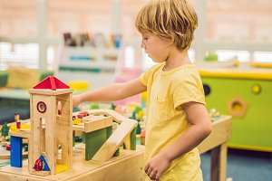 Children play with wooden toy, build