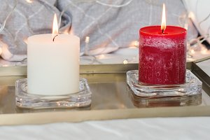 Two burning candles on tray