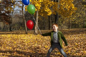 red-haired boy in autumn park