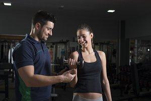 Man helping woman training biceps at