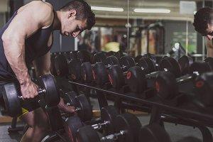 Man training biceps muscle at gym