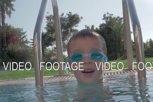 Cheerful child in goggles bathing in