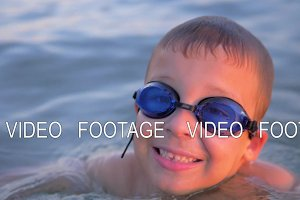 Smiling child in goggles swimming in