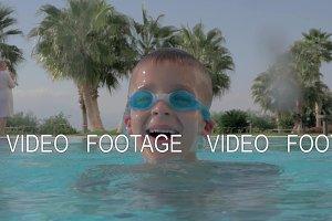 Cheerful boy bathing in swimming
