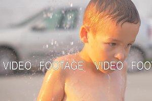 Child taking outdoor beach shower