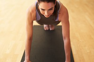 Fit woman doing push ups in a gym.jpg