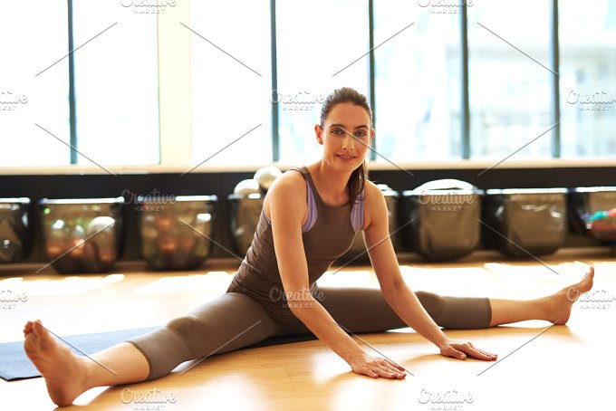 Fit woman is stretching on mat.jpg - Sports