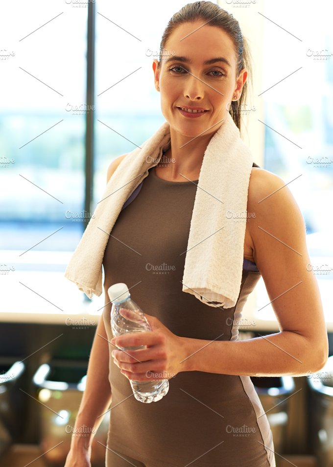 Smiling Fit Young Woman Holding a Bottle of Water.jpg - Sports