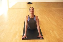 Thoughtful Young Woman Stretching on Yoga Mat.jpg