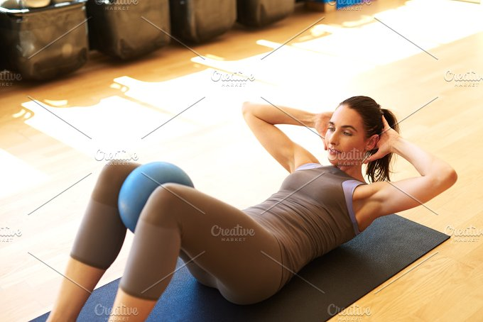 White woman doing pilates with ball.jpg - Sports