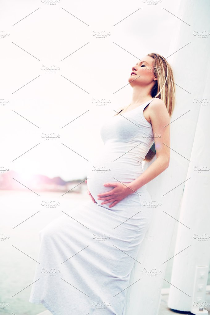 Pregnant woman relaxing against a white pillar.jpg - People
